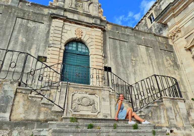 Old church with pretty stairs with me sat on the bottom step inside Dubrovnik Old Town