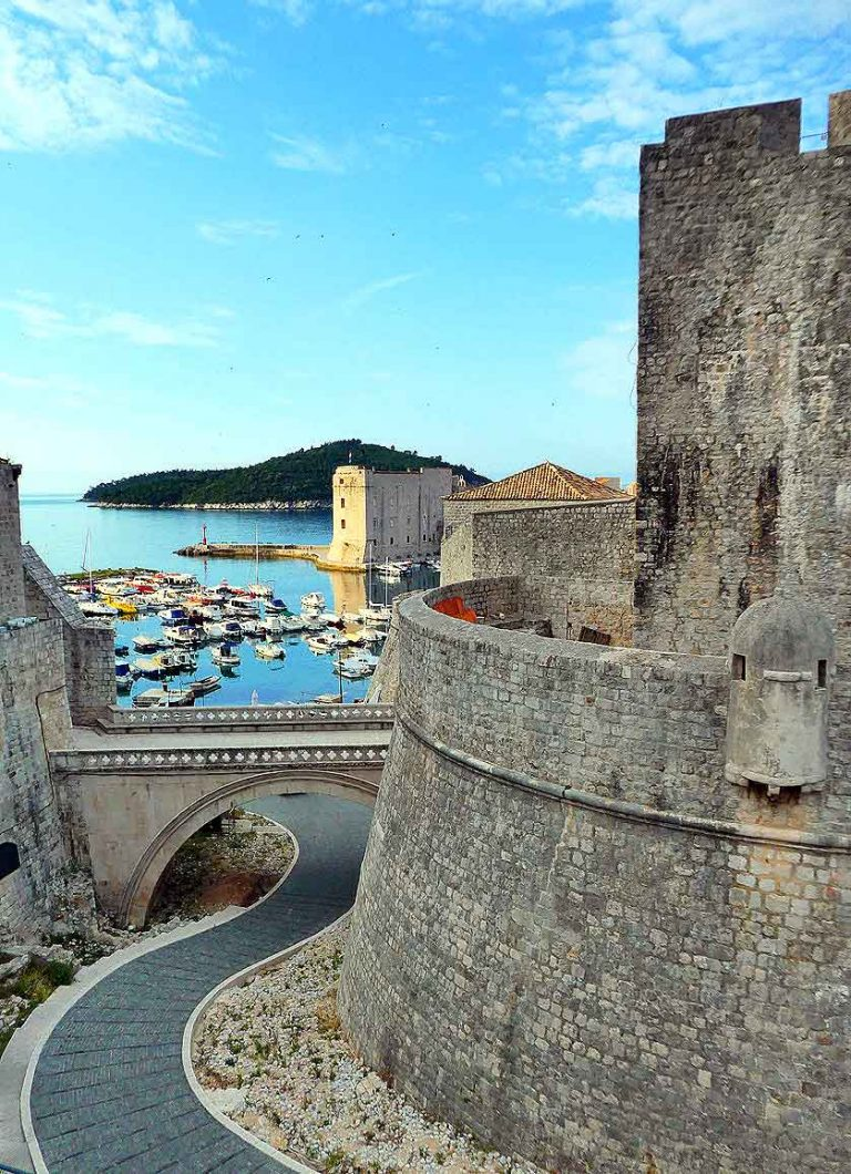 Early morning sunlight outside of Dubrovnik City Walls looking throuhg an archway at the harbour
