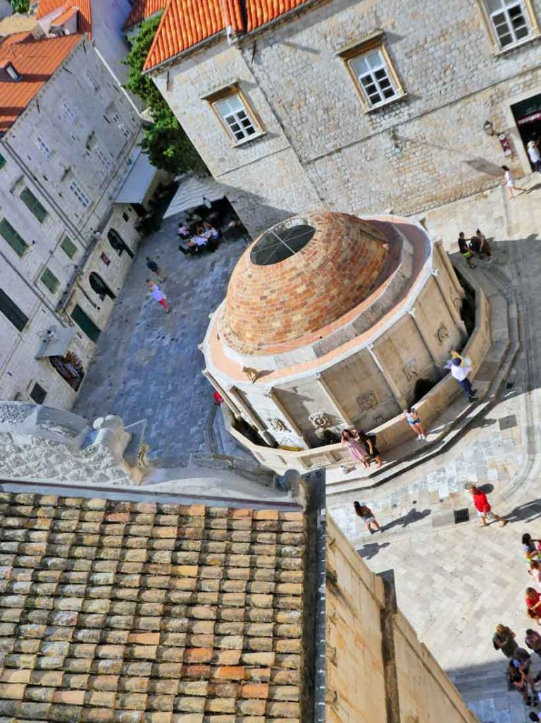Looking down on the water fountain, red roofs and cobbled streets from the Old City Wall of Dubrovnik