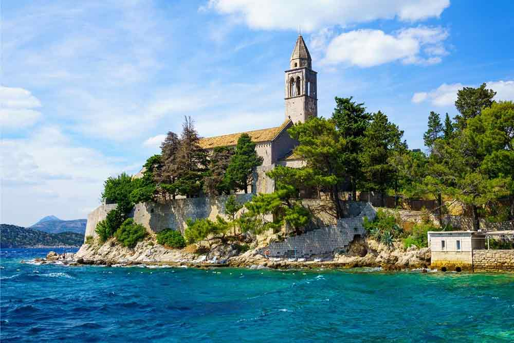 Church on an island surrounded by trees. surrounded by the blue sea and blue skies. The Elefiti islands are an easy day trip from Dubrovnik.