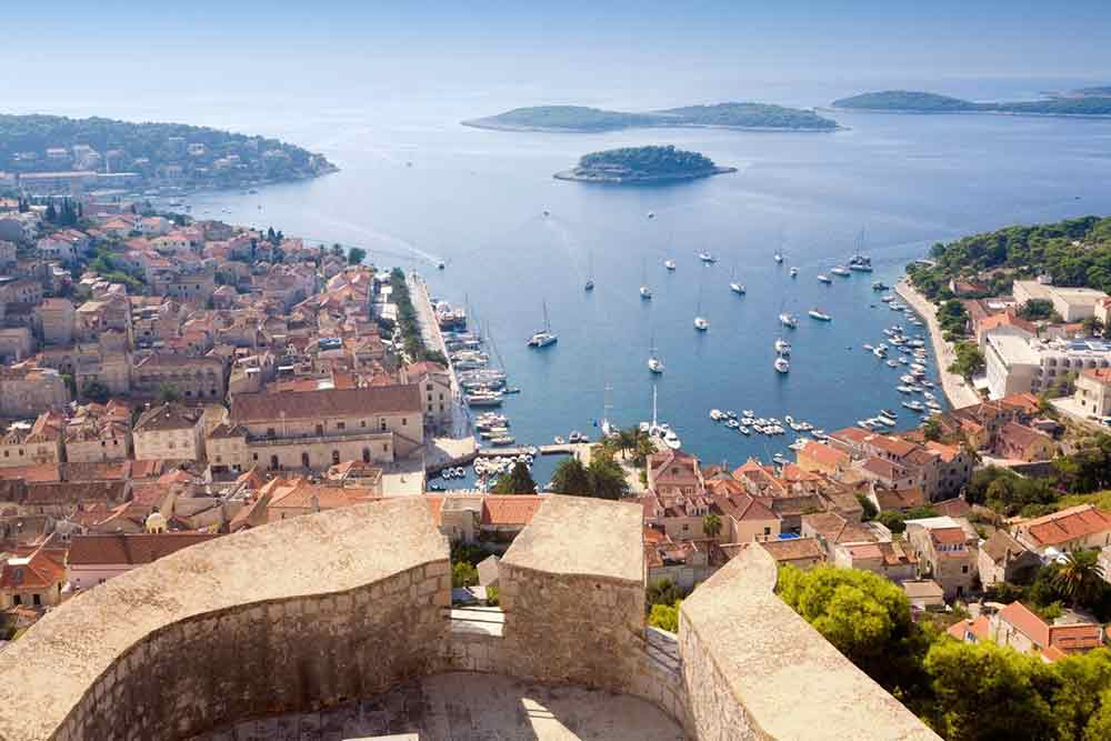The view over Hvar from the citadel. looking out over the ocean with a hazy blue sky and small islands in the background