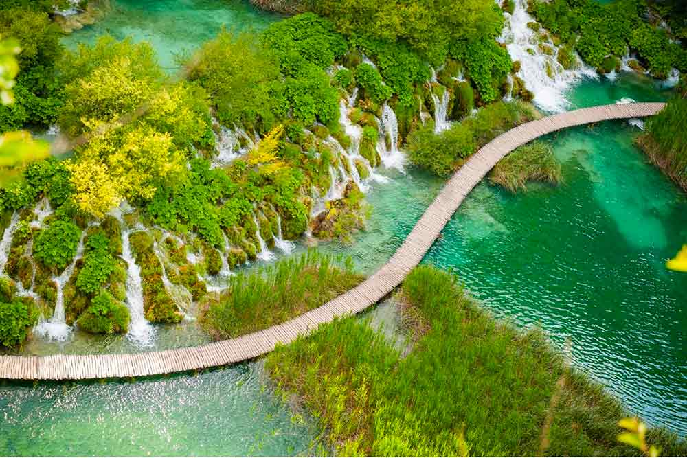 view of plitvice lakes from above, looking down on waterfalls and the boardward at the UNESCO listed site in Croatia. You can visit the lakes on a day trip from Dubrovnik