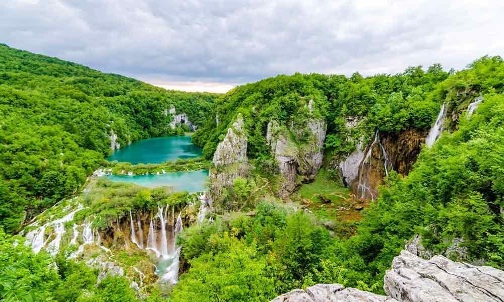 Plitvice lakes in croatia, image of waterfalls and cascades with lakes in a green valley and a moody grey sky