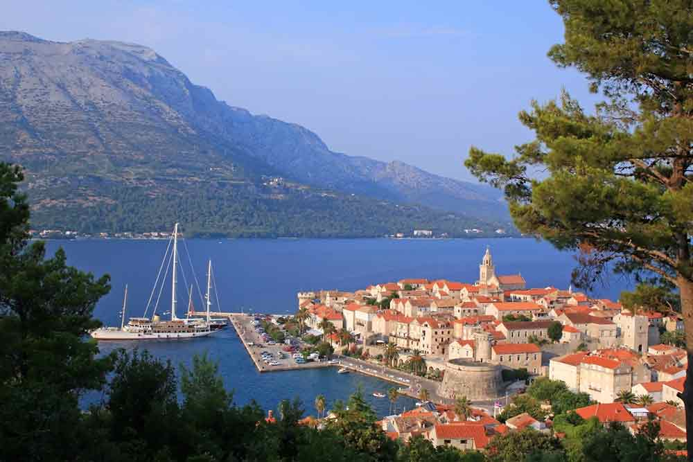 the city of korcula in croatia with blue sea and a mountain behind it, there are some boats in the sea surronding the city