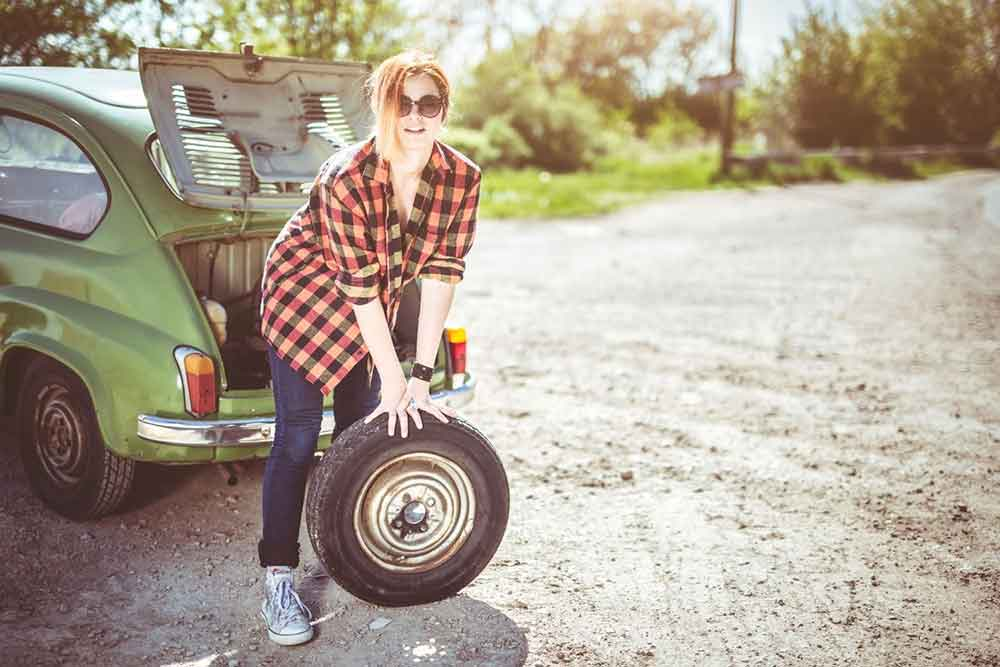 Lady on a dusty road wearing a checkered shirt changing a car tyre