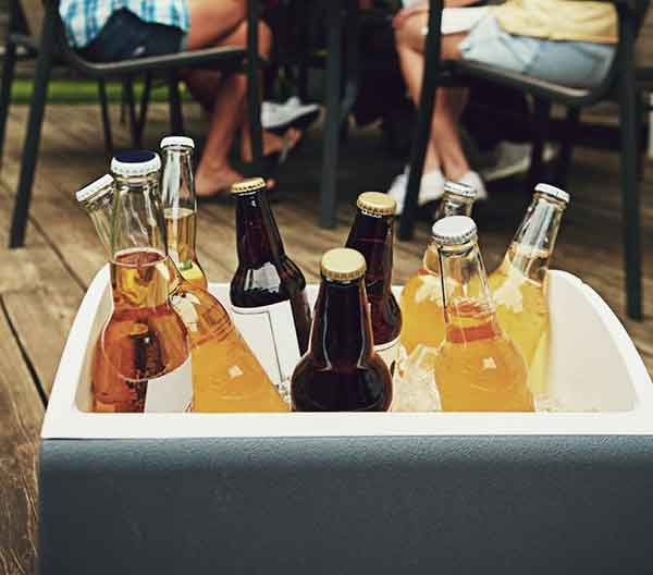 a cooler box filled with ice and bottles of beer with a burred image of people sitting and drinking in the distance