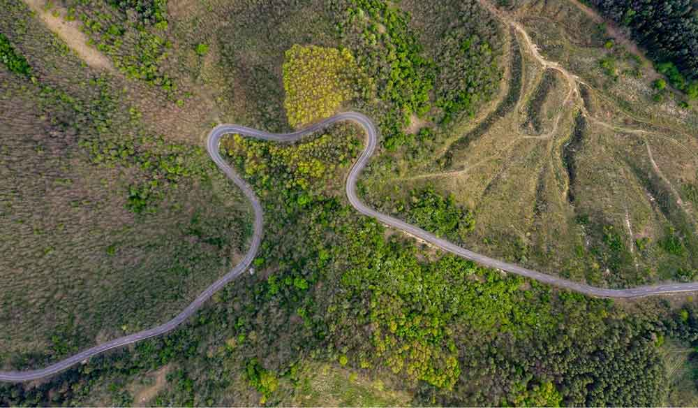 a drone shot of the countryside with an empty road winding through it