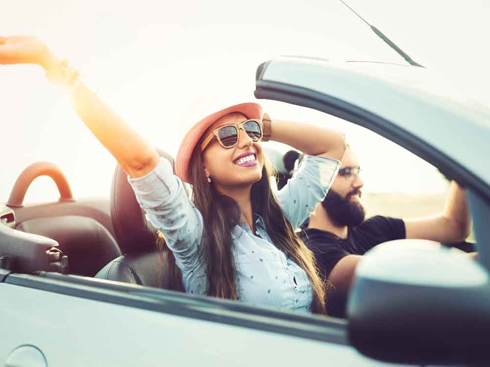 Two people in a convertible car on a road trip.
