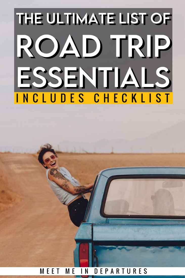 essentials for a road trip packing title pin with a woman smiling and hanging out the window of a blue car. This article features a list of over 70 road trip essentials.